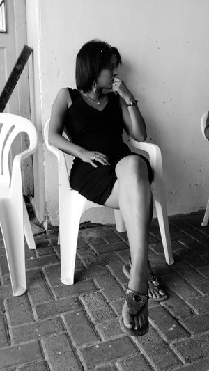 Woman Deep In Thought Black Dress White Wall Sandals Looking Sideways Legs Young Woman