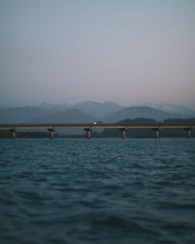 Bridge over river against clear sky at dusk