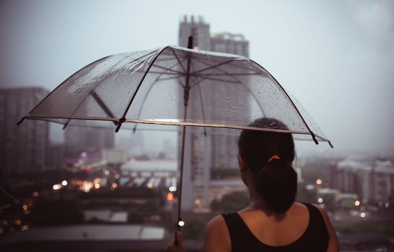 Rear view of woman with umbrella in rain