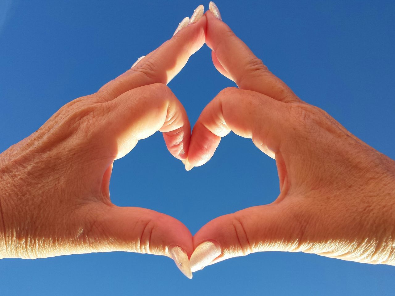Cropped Image Of Hands Forming Heart Shape Against Clear Sky