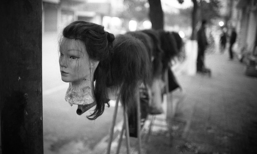Close-up of mannequins with wig at street