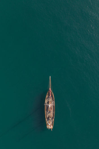 top down aerial view of a tall mast sailing boat on a calm turquoise ocean with copy space
