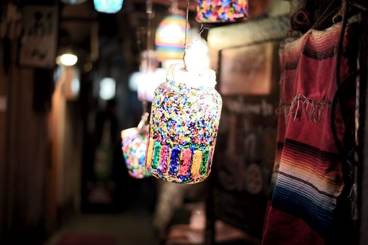 Illuminated lanterns hanging in store for sale