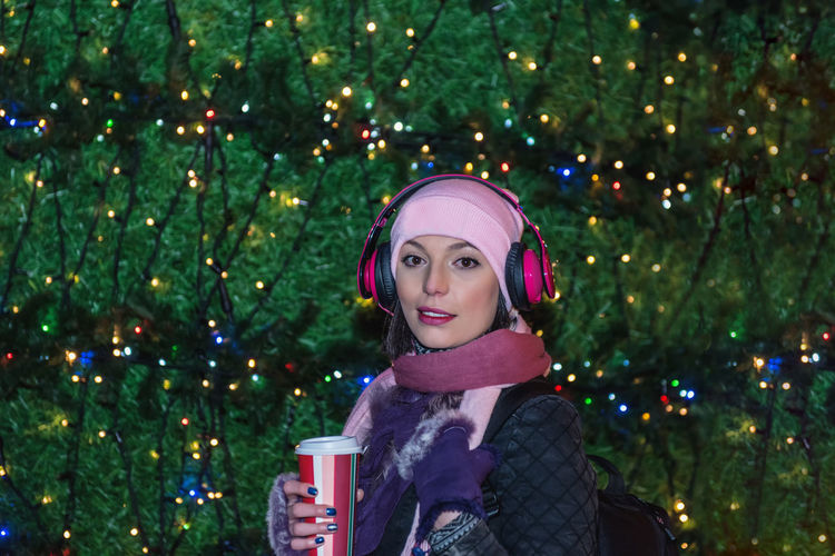 Portrait of woman against christmas tree