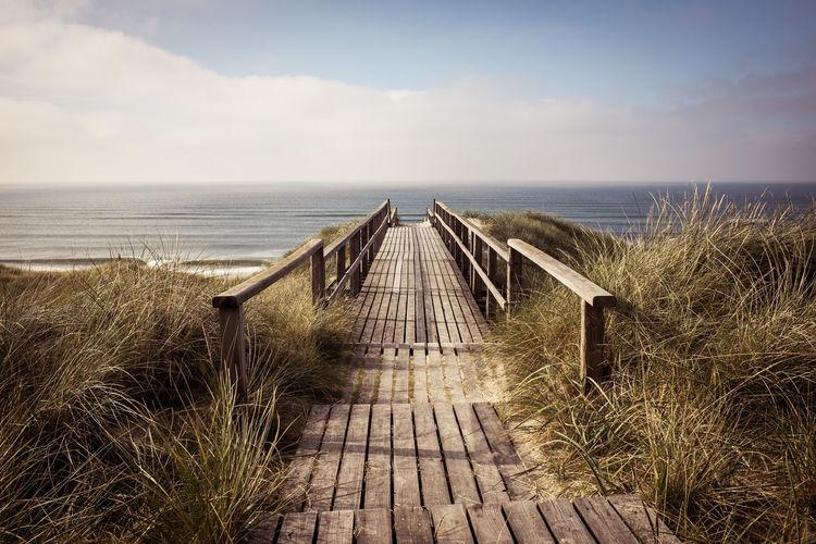 Empty boardwalk leading to calm sea against cloudy sky