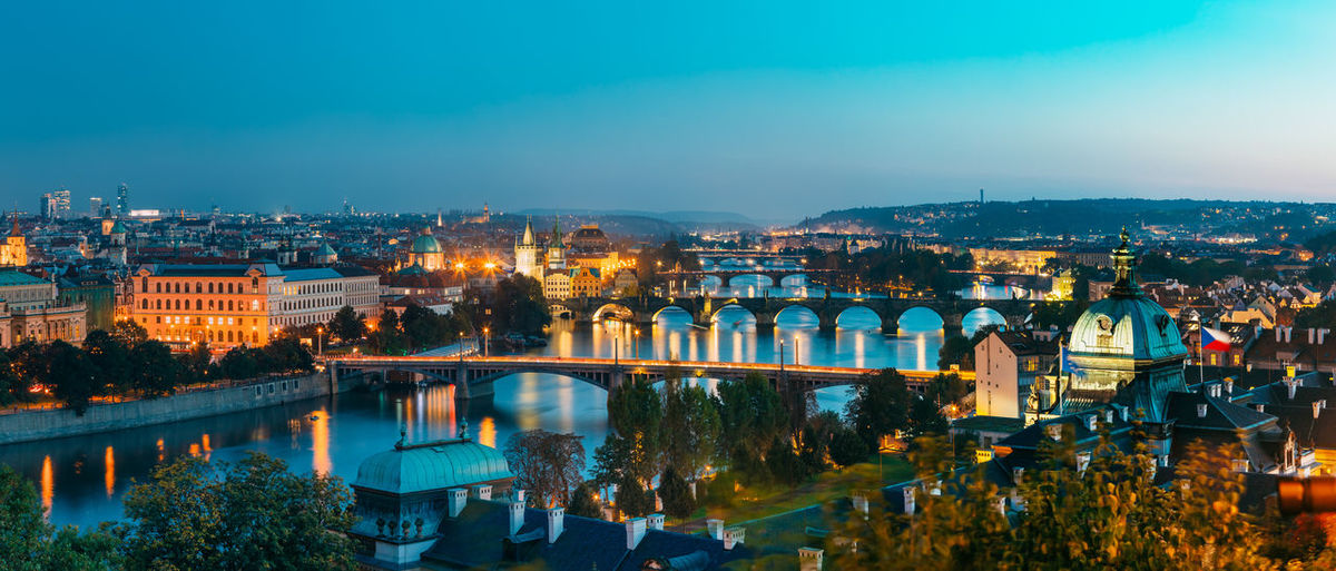 Illuminated bridges over river in city at dusk