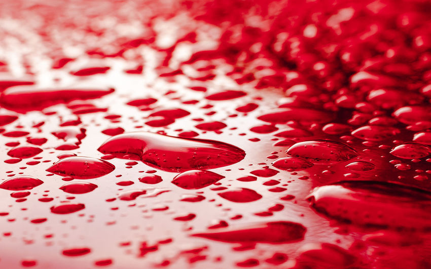 Surface level of water drops on red surface