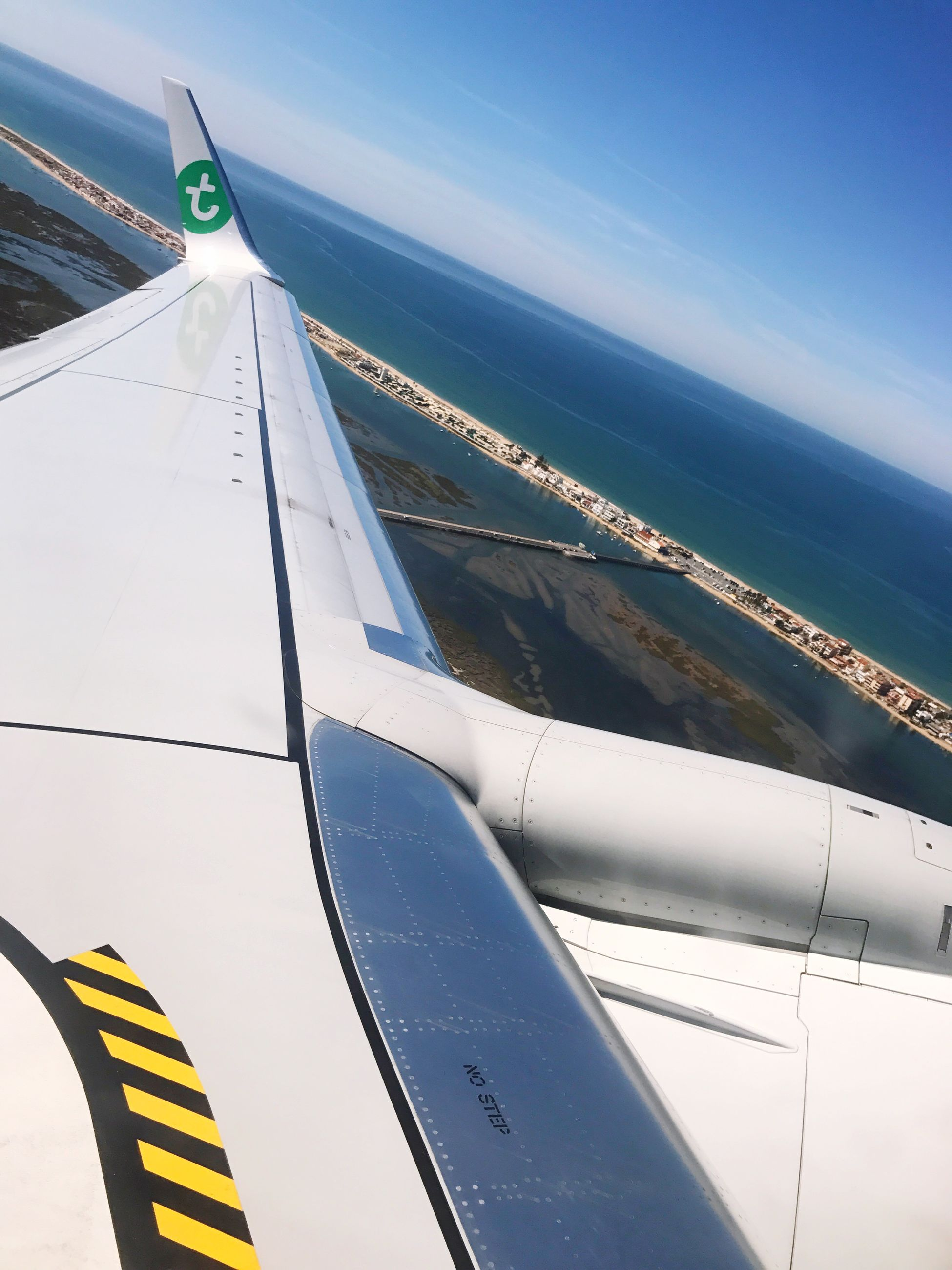 airplane, transportation, air vehicle, mode of transport, no people, day, aircraft wing, sea, outdoors, blue, flying, sky, airplane wing, water, nature, close-up