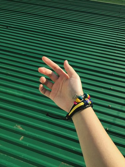 Cropped hand by green corrugated iron