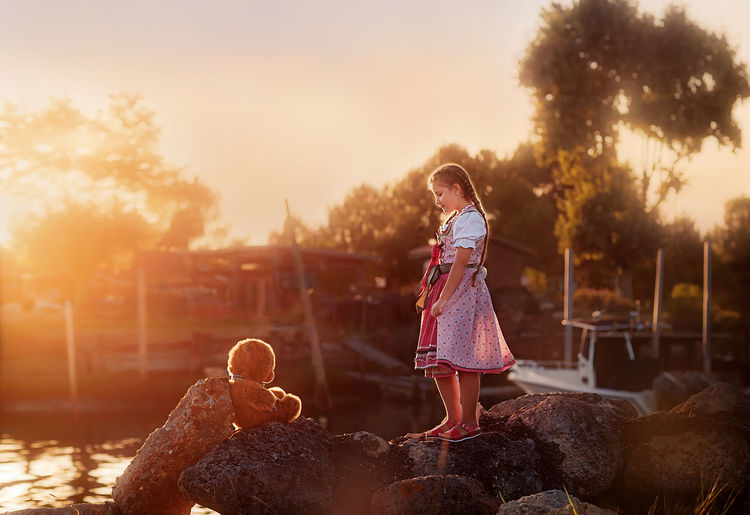 Girl standing on rock by stuffed toy against sky during sunset