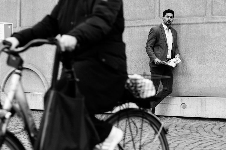 Midsection Of Woman Riding Bicycle Against Businessman On Footpath