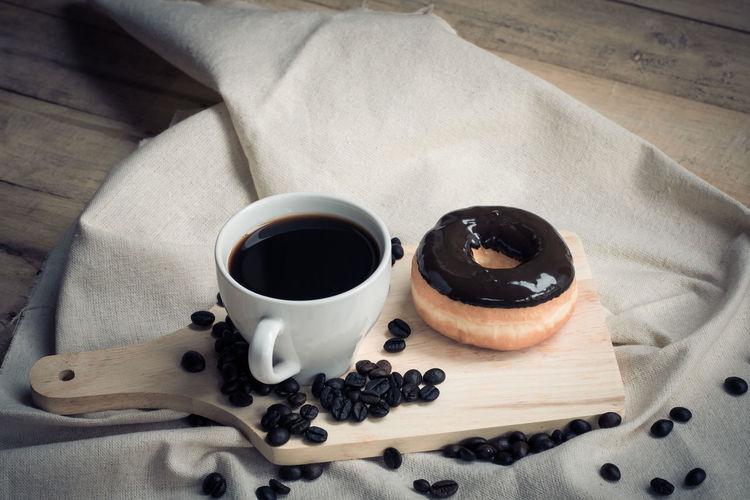 High angle view of roasted coffee beans with chocolate donut and black coffee cup on wooden table