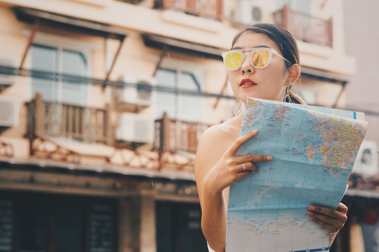 Low angle view of mid adult woman with world map standing against building