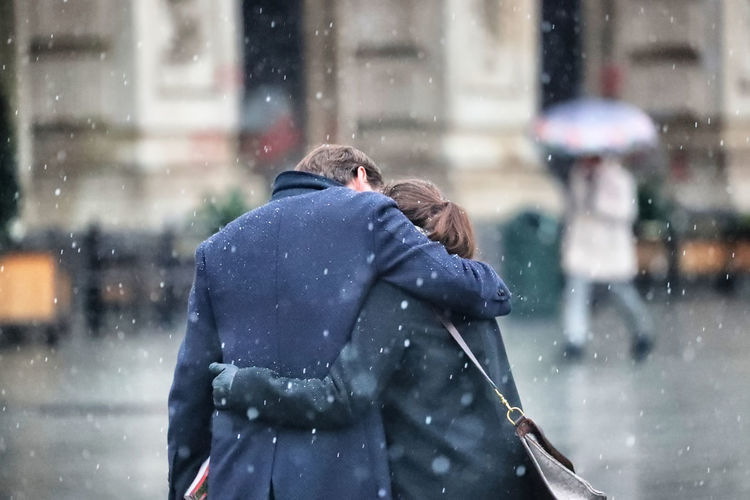 Rear view of couple embracing in city during snowfall