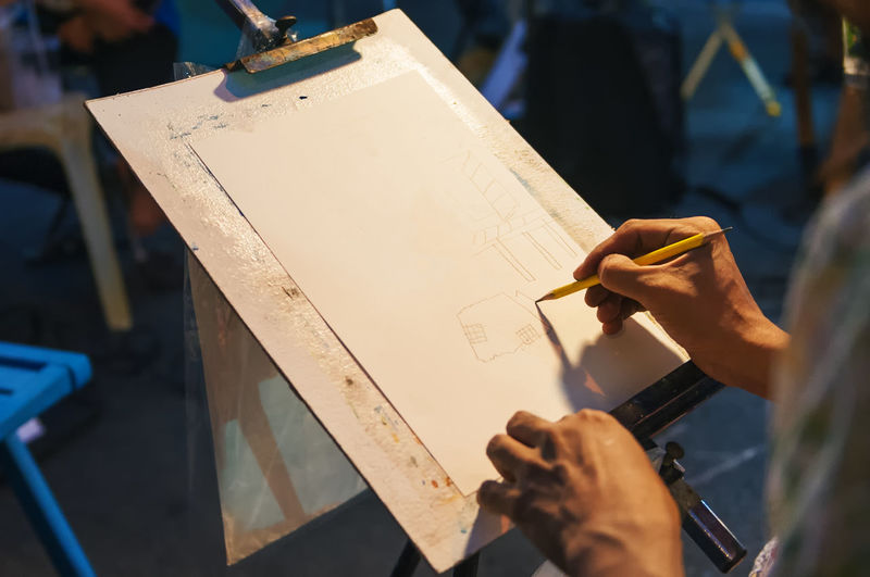 High angle view of person drawing on paper