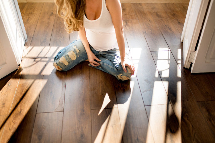 High angle view of woman sitting on hardwood floor at home