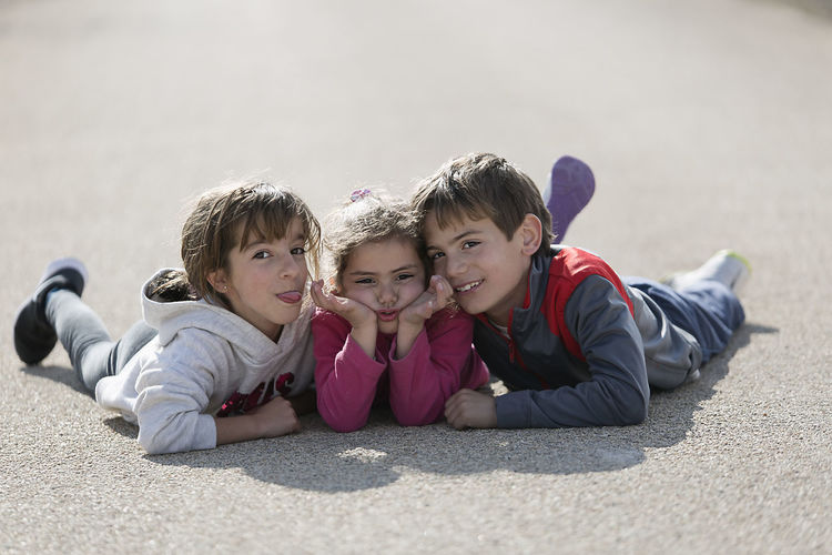 Three children lying on the floor one on top of the other. Horizontal shot with natural light Children Children's Portraits Spanish Tree Children Boys Caucasian Ethnicity Child Childhood Day Elementary Age Girls Happiness Leisure Activity Lifestyles Looking At Camera Looking At The Camera Lying Down Outdoors People person Portrait Real People Smiling Togetherness