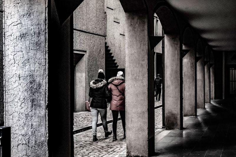 Rear view of men walking in building