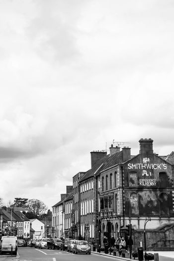 Buildings by road in city against sky