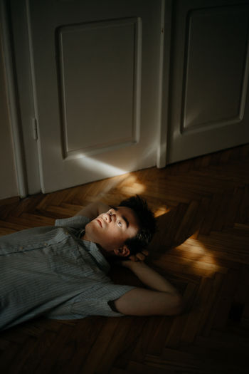 Portrait of a young man laying on floor while illuminated by sun