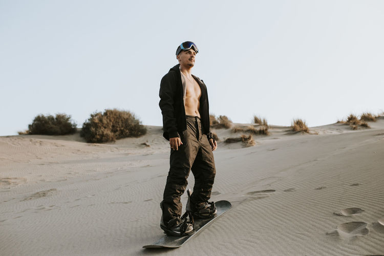 Full length of young man standing on sand