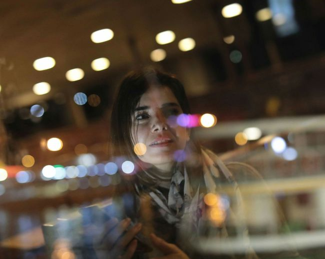 Young woman with illuminated lights at night