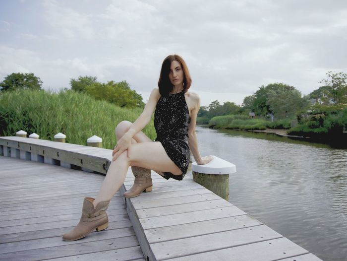 Portrait Of Sensual Woman Sitting On Pier Over River Against Cloudy Sky