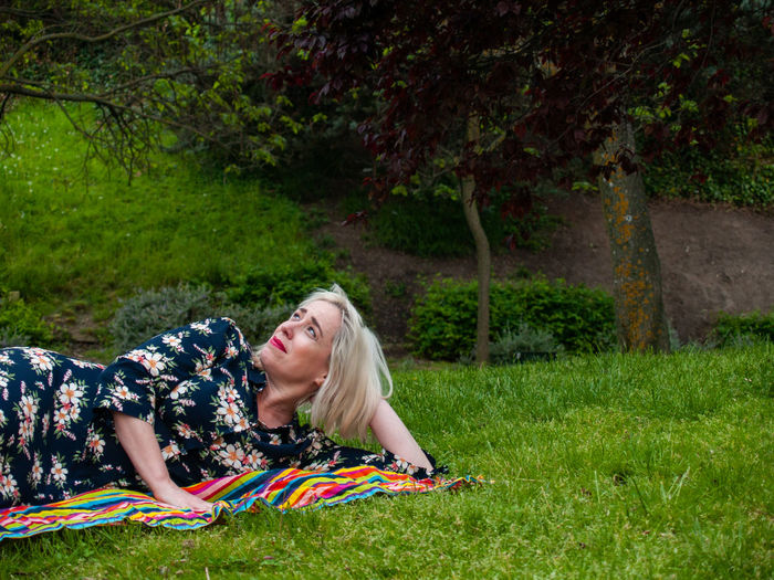 Mature woman lying on picnic blanket at park