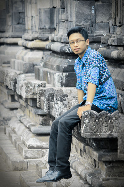 Batik Batik Style Temple People Person Men Fashion Old Antique Blue Ads Calm Stone Rock Outdoors One Person Sitting Casual Clothing Steps Full Length Young Adult Built Structure Eyeglasses  One Man Only Day