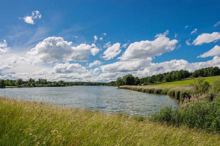 Scenic view of river against cloudy sky on sunny day