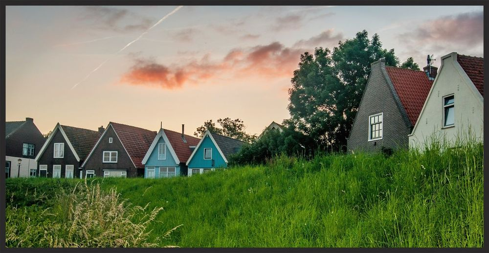 Houses on field against sky at sunset