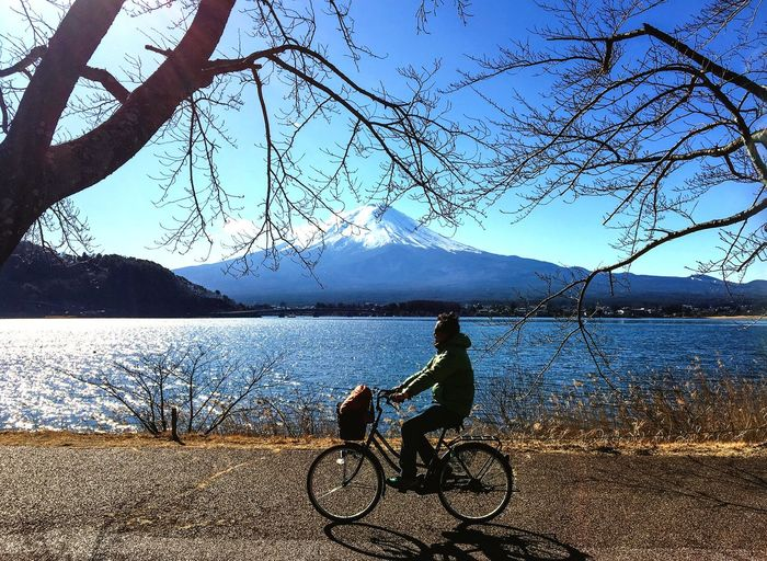 Man with bicycle on lake against sky