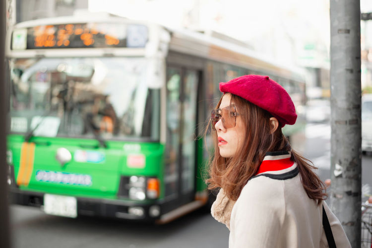 Side view of woman looking away while standing on street