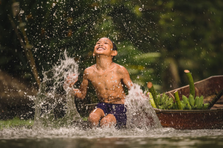 Happy shirtless boy splashing water while sitting on boat in river