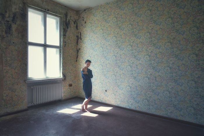 Full length of woman standing against wall at home