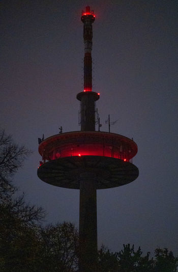 Low angle view of illuminated tower against sky at dusk