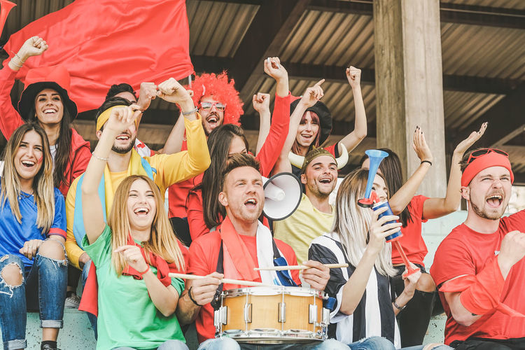Excited people sitting with musical instruments in stadium