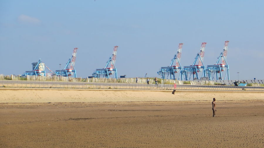 Cranes Metal Structures Statue Another Place By Anthony Gormley Beach Blue Clear Sky Day Men Nature Oil Pump One Person Outdoors People Real People Sand Sky