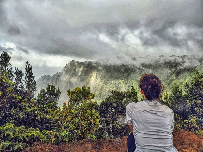Silhouette of man standing on mountain against cloudy sky