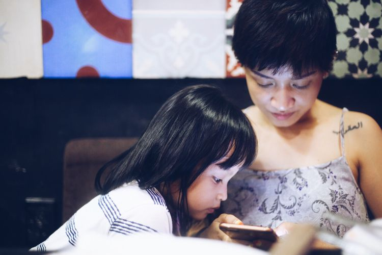 Girl Looking At Woman Using Mobile Phone At Restaurant