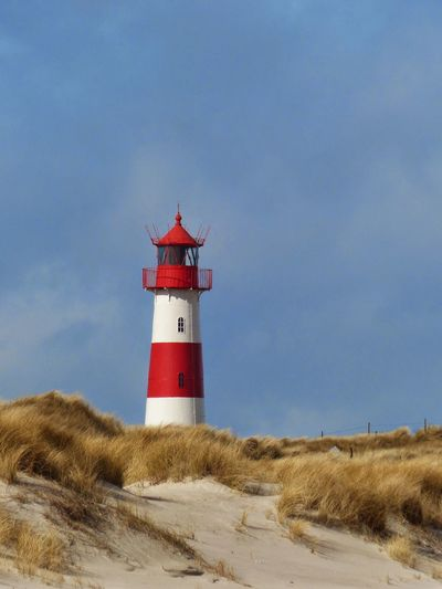 Guidance Lighthouse Direction Protection Built Structure Architecture Safety Security Tower Building Exterior Sky Blue Red Cloud Outdoors Calm Tall Shore Tranquility Nature Sylt