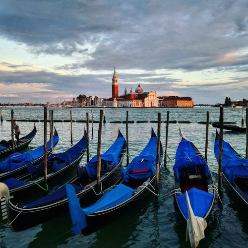 Gondola boats moored by wooden posts in grand canal against cloudy sky during sunset