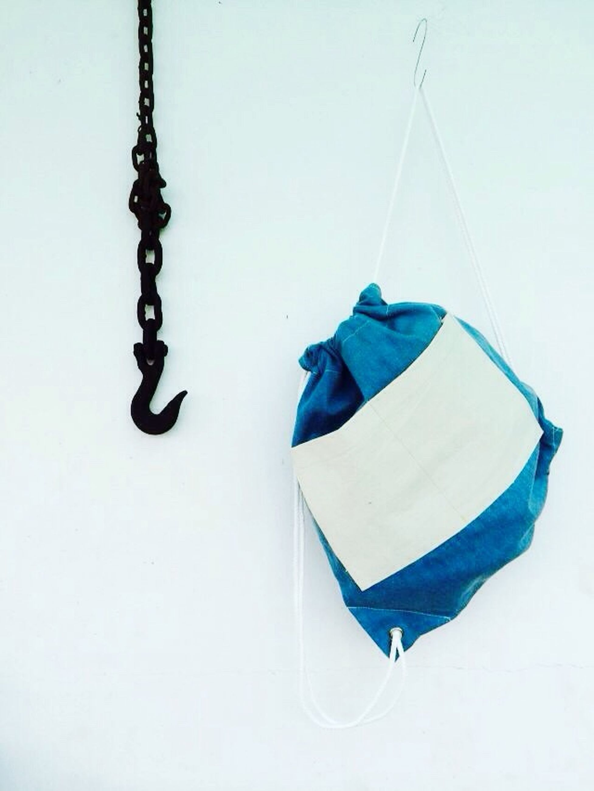 studio shot, white background, still life, hanging, copy space, single object, close-up, rope, blue, two objects, absence, no people, high angle view, metal, table, man made object, creativity, chain, white color, group of objects