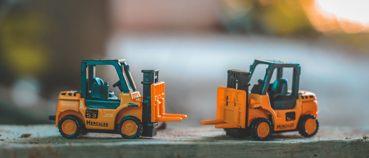 Close-up of yellow toy forklifts on wood