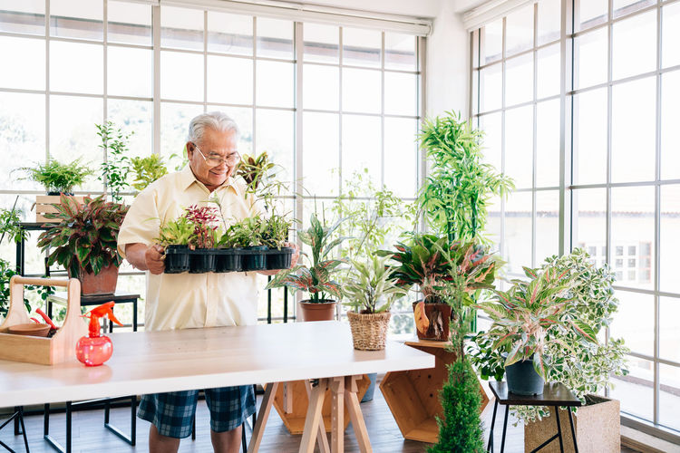 Man standing by potted plant on table