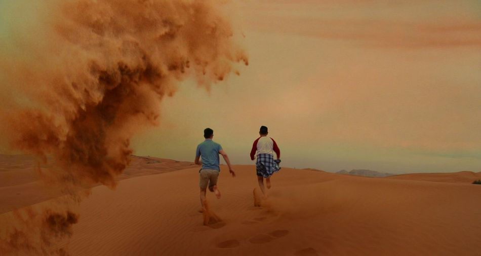 Rear view of two men running on sand dune