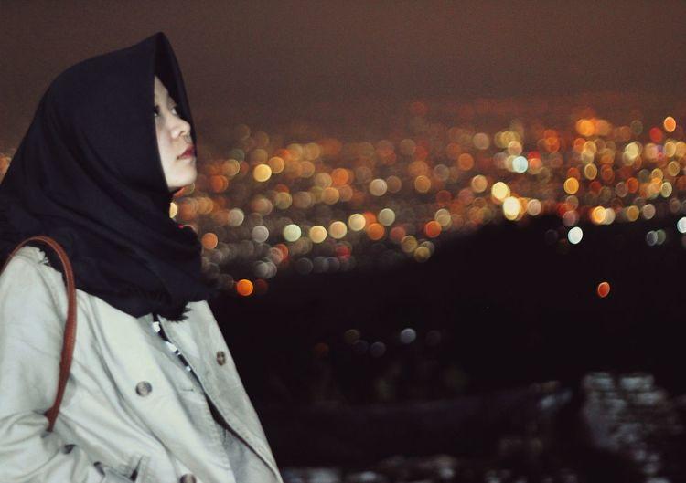 Side view of man looking at illuminated city at night
