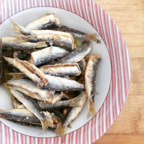 Grilled anchovies fish with olive oil on plate Above Anchovies Board Close-up Dinner Food Food And Drink Gourmet Healthy Eating Healthy Lifestyle Indoors  Lunch Meal Mediterranean  Plate Ready-to-eat Sardine Sardines Seafood Table Tasty Top View Variation Wooden
