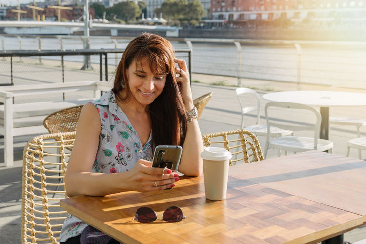 Young woman using mobile phone while sitting at camera