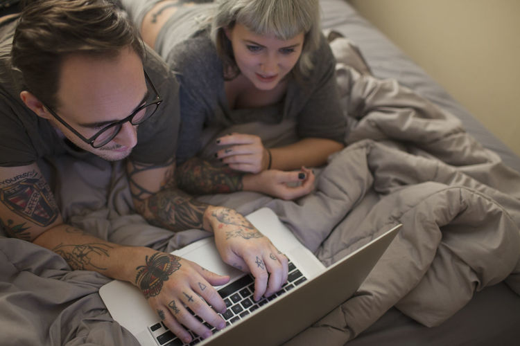 High angle view of woman using laptop on bed